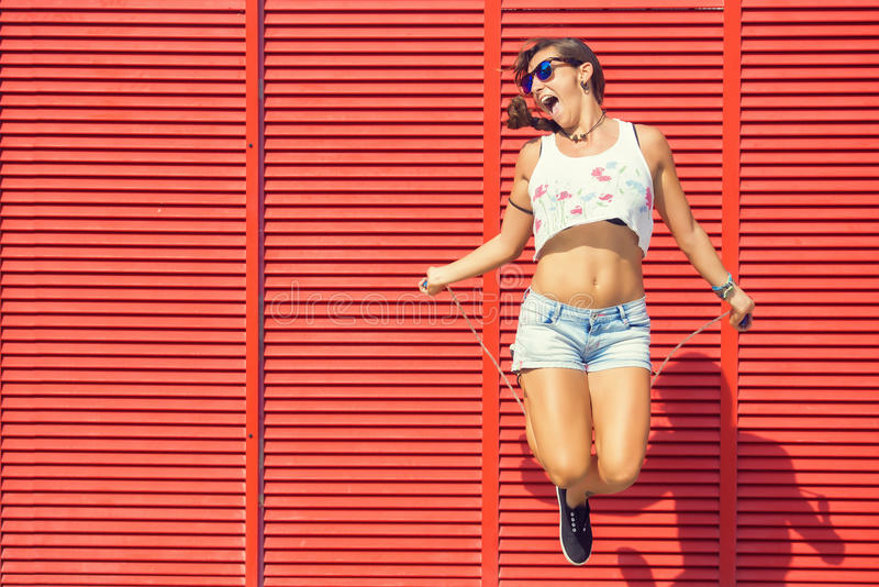 Woman jumping rope. On red background stock photos
