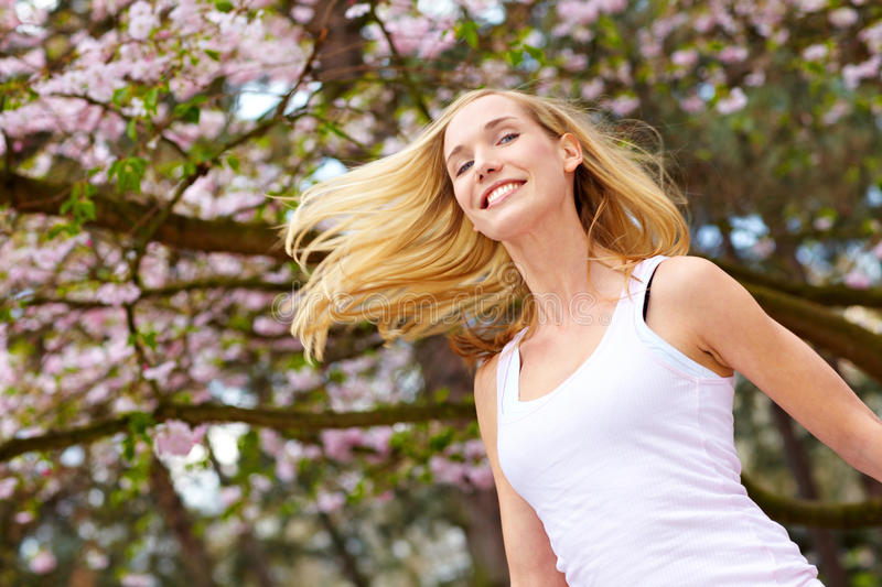 Woman jumping under cherry tree royalty free stock images