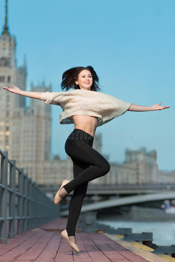 Woman jumping on waterfront. Young woman jumping on the waterfront with outstretched arms to the sides stock photos