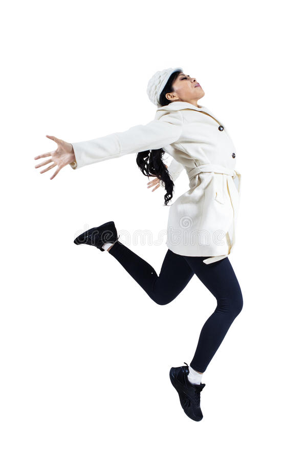 Woman jumping with winter coat. Asian woman jumping with winter coat, isolated on white background royalty free stock image