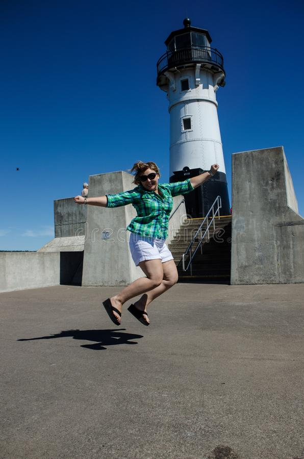 Woman jumps in front of the Canal Park Lighthouse in Duluth Minn royalty free stock image