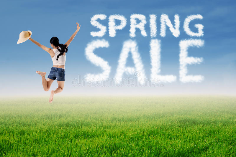 Woman jumps with spring sale cloud royalty free stock photo