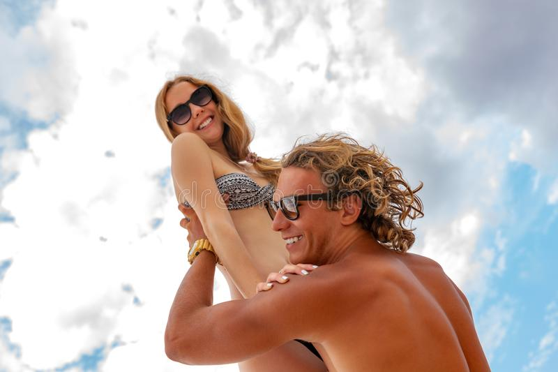 Woman jumps to the man in his arms, standing in the sea. Both are in the swimsuits. Smiling playful young couple in love. Woman jumps to the men in his arms stock images