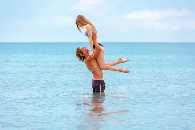 Woman jumps to the man in his arms, standing in the sea. Both are in the swimsuits. Smiling playful young couple in love. Woman jumps to the men in his arms royalty free stock image