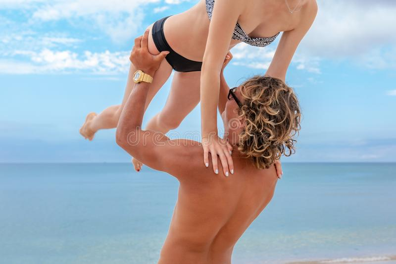 Woman jumps to the man in his arms, standing in the sea. Both are in the swimsuits. Smiling playful young couple in love. Woman jumps to the men in his arms royalty free stock images