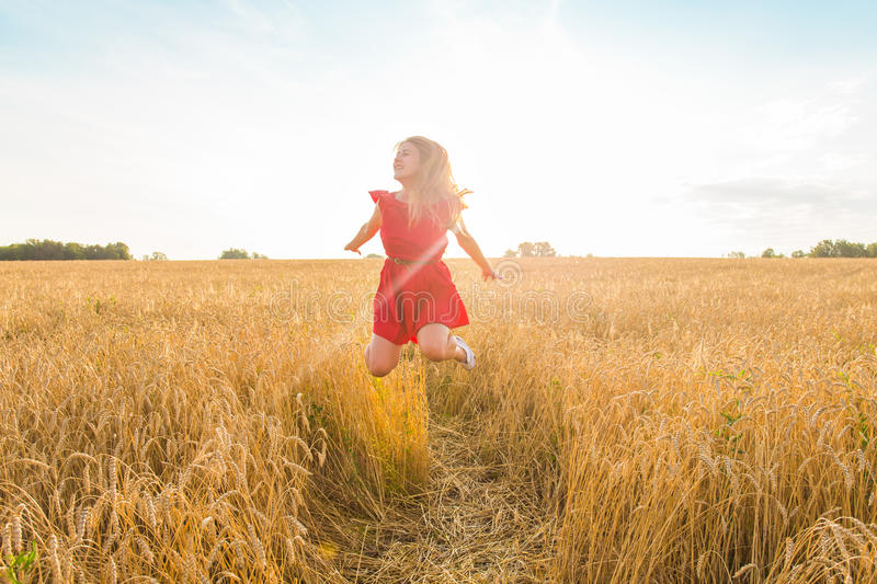 Woman jumps to the sky in yellow field at sunset. Happy woman jumps to the sky in the yellow meadow at the sunset stock photo