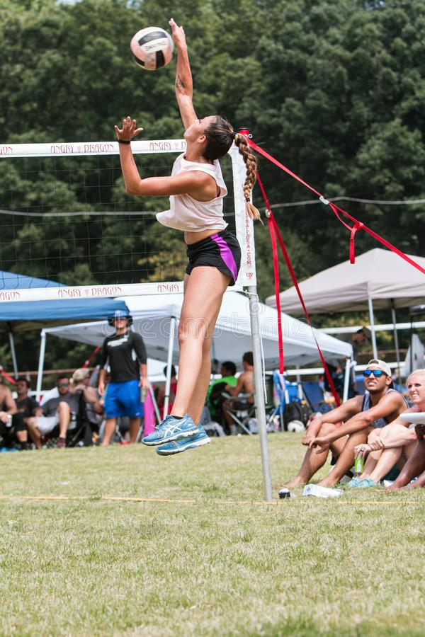 Free Woman Jumps To Spike Ball In Triples Grass Volleyball Tournament Stock Photography - 157344702