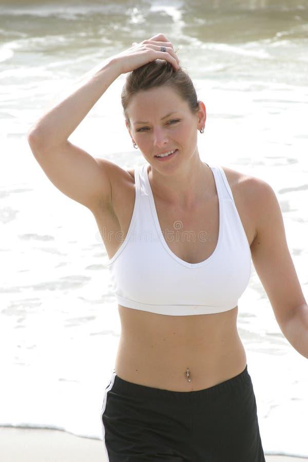 Woman just finishing run on beach royalty free stock image