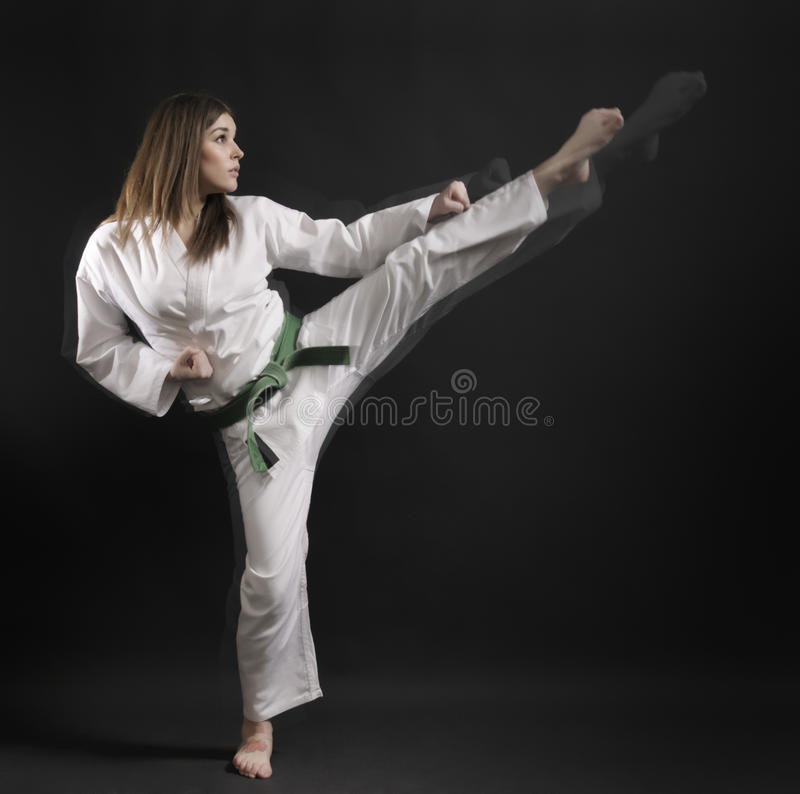 Woman of karate performs a high kick- 01. royalty free stock image