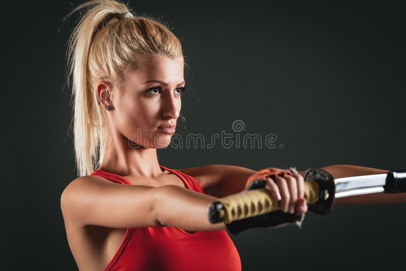 Woman With Katana. Pretty girl with a serious expression on her face drawing sword royalty free stock images