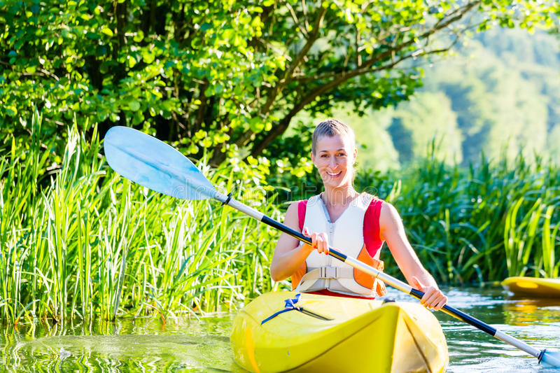 Woman with kayak or canoe on river stock photo