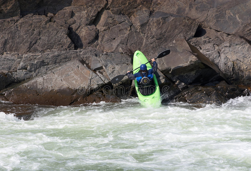 Woman on the kayak launching into the river from the rocks royalty free stock photos