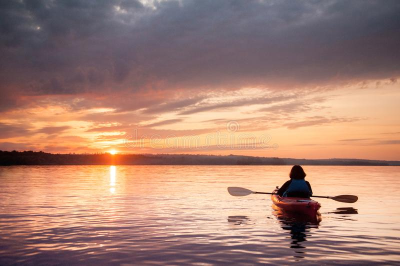 Woman in a kayak on the river on the scenic sunset.  royalty free stock photos