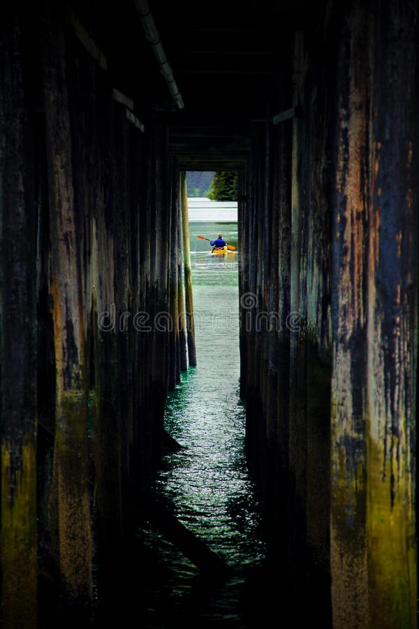 WOMAN ON KAYAK ROWING ON PEACEFUL LAKE. Seen through wooden pier logs royalty free stock images