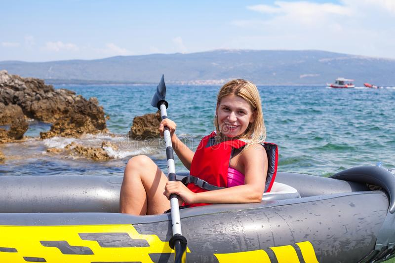 Woman kayaking in Croatia. Happy young woman kayaking in the adriatic sea, near by Krk island, Croatia stock photo