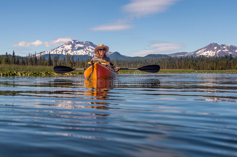Woman kayaking on mountain lake near Bend, Oregon. Woman in a kayak on Hosmer Lake near Bend, Oregon, in the Deschutes National Forest. Peaks of the Cascade stock images