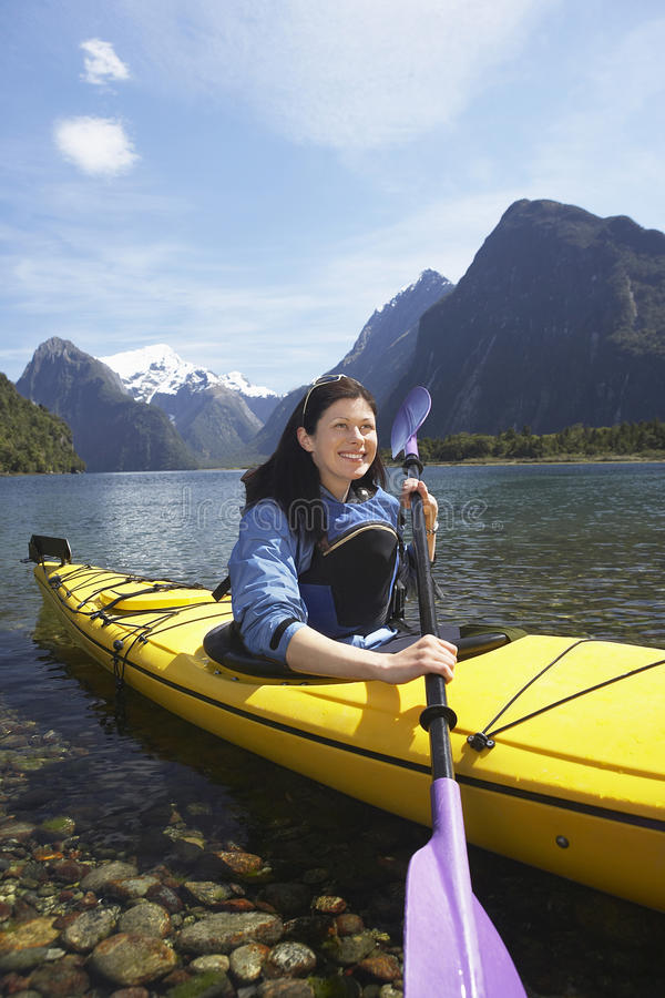 Woman Kayaking In Mountain Lake stock photos