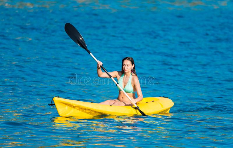Woman Kayaking  in the open sea stock photography