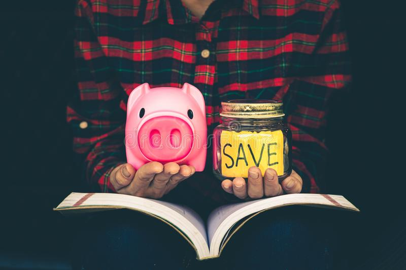Woman keep the money in the piggy bank to be used for educational purposes, Banking and saving concept stock images