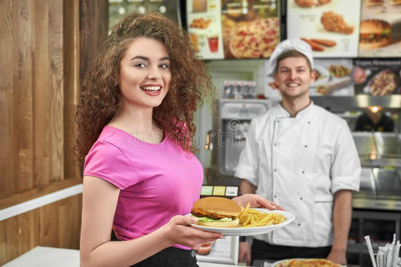 Woman keeping plate with fast food and smiling in cafe. royalty free stock photos