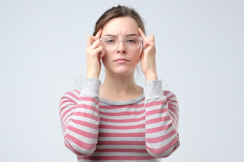 Woman keeps fingers on temples. migraine concept stock photo