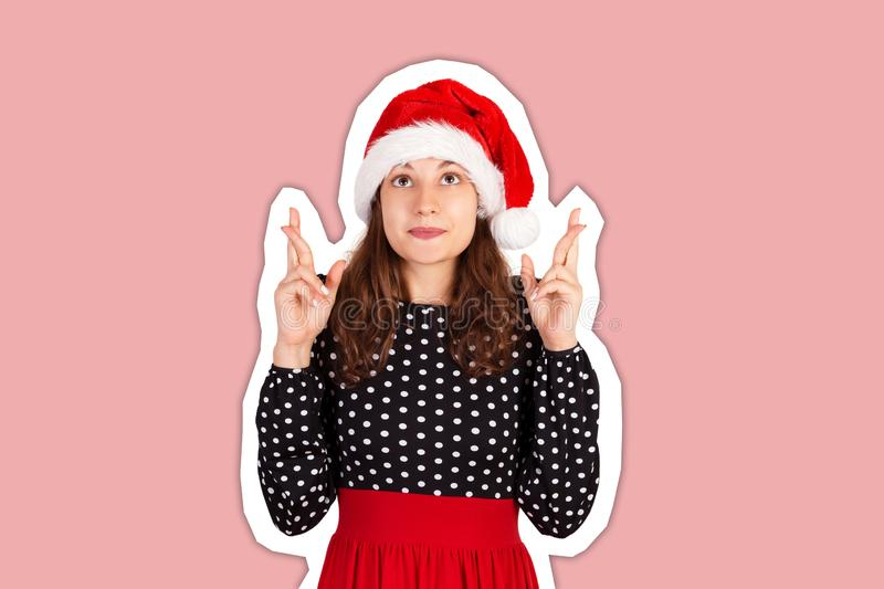 Woman keeps hands raised, fingers crossed and dreams about something. Magazine collage style with trendy color background. holiday stock photos