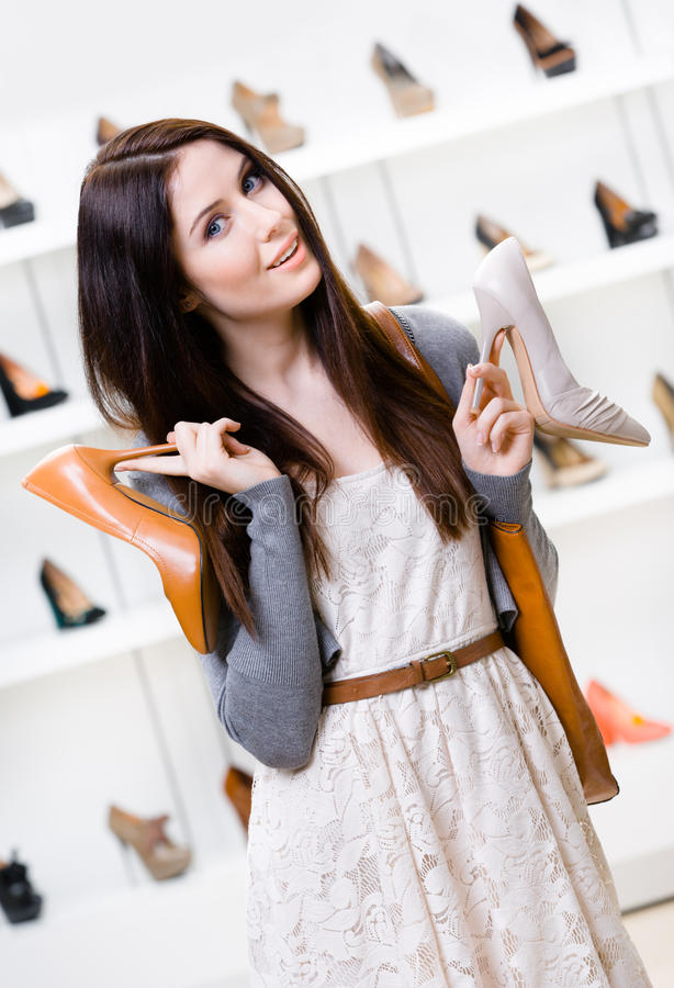 Woman keeps two shoes in the shopping mall. And can't choose the one for her royalty free stock photo