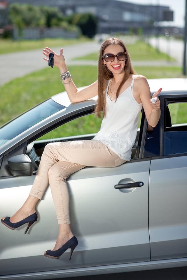 Woman with keys and lisence near her car. Young woman holding keys to new car smiling at camera and sitting on the car door royalty free stock photos