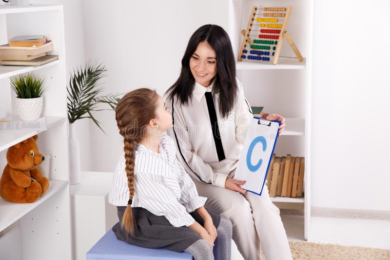 Woman with kid girl training speech together sitting in the white room. Woman with kid girl training speech together sitting in the white room royalty free stock photography
