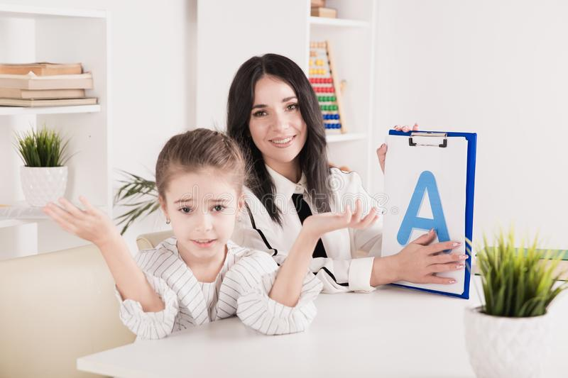 Woman with kid girl training speech together sitting in the white room. Woman with kid girl training speech together sitting in the white room stock photo