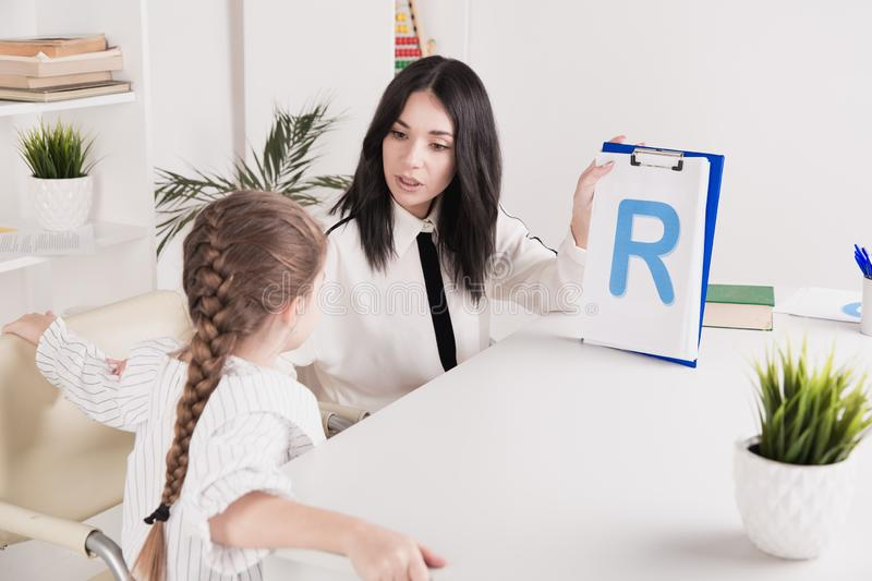 Woman with kid girl training speech together sitting in the white room. Woman with kid girl training speech together sitting in the white room stock images