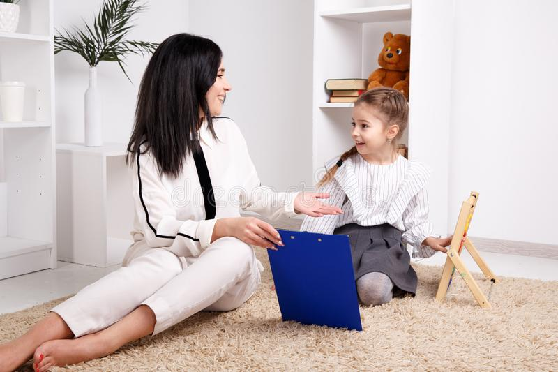 Woman with kid girl training speech together sitting in the white room. Woman with kid girl training speech together sitting in the white room royalty free stock image