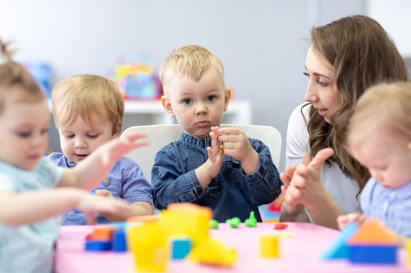 Woman teaches children modeling plasticine in day care center royalty free stock photo