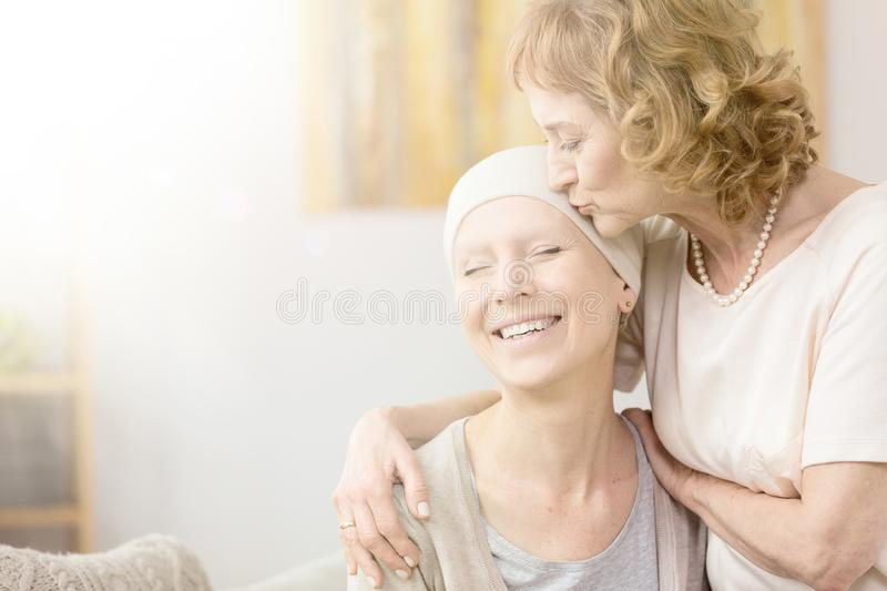 Woman kissing cancer survivor`s temple. Elderly women kissing happy cancer survivor`s temple, comforting her friend stock images