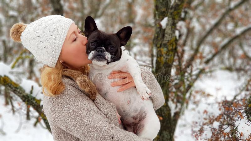Woman kissing a french bulldog in the snow stock image