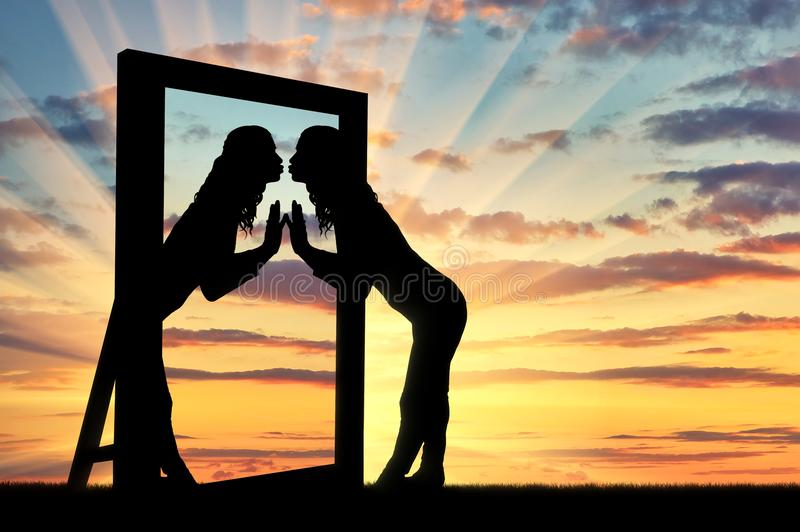 Woman is kissing her reflection in the mirror stock image