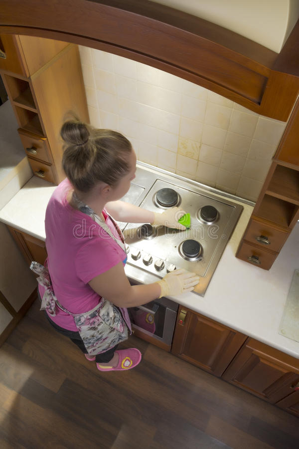 A woman in the kitchen cleans a gas stove. royalty free stock photos