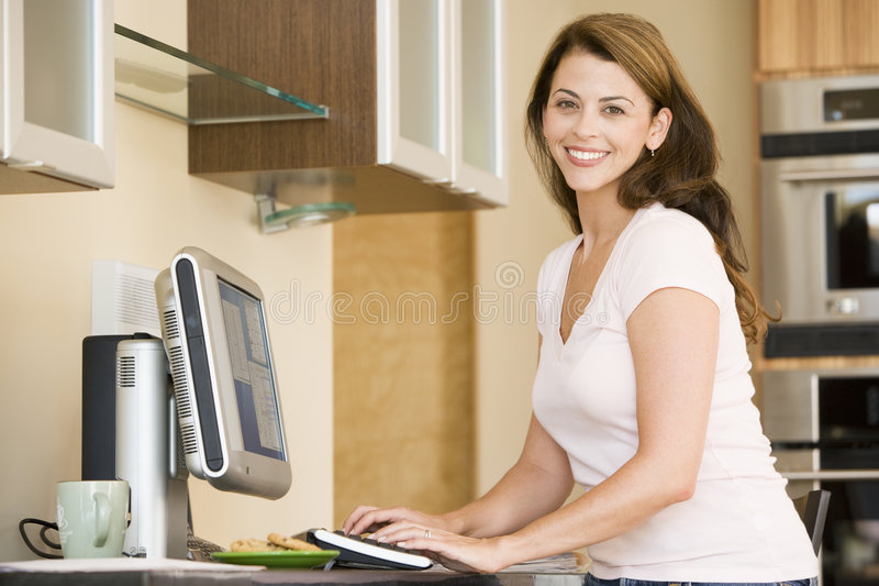 Woman in kitchen with computer smiling royalty free stock photography