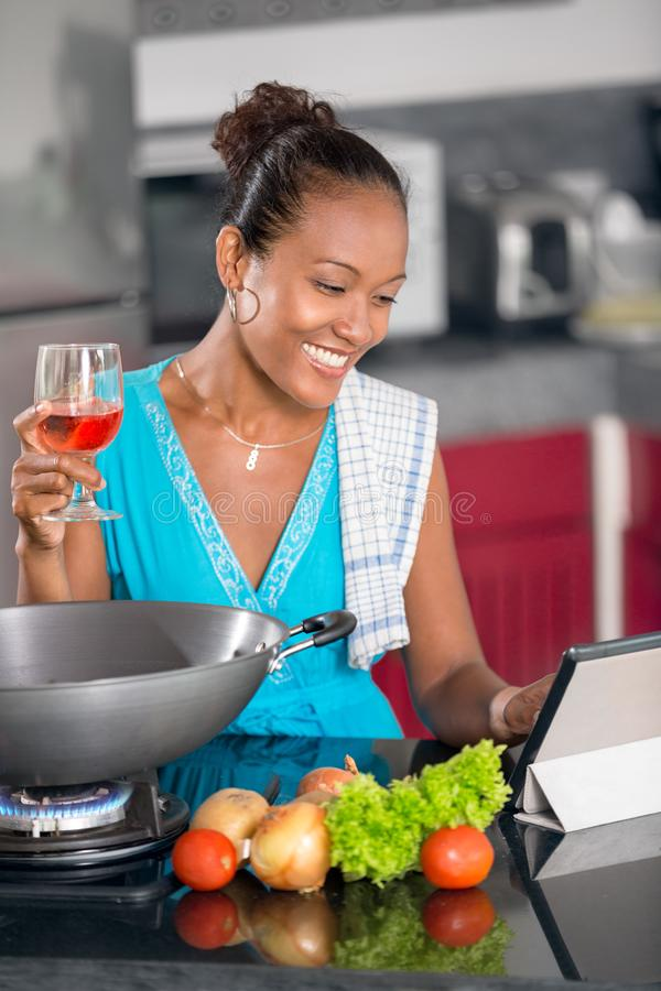Woman in kitchen following recipe on digital tablet royalty free stock photography