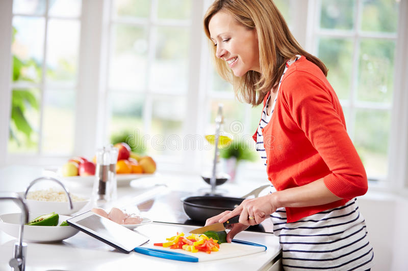 Woman In Kitchen Following Recipe On Digital Tablet stock image