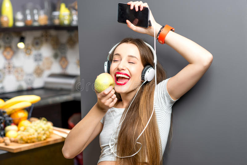 Woman in the kitchen. Lifestyle portrait of a young sports woman listening to the music with phone and headphones in the modern kitchen interior full with fruits royalty free stock photo