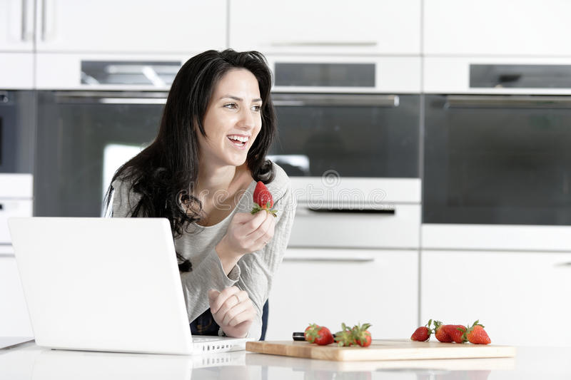 Woman in kitchen reading recipe. Beautiful young woman reading a recipe from a laptop in her kitchen stock image