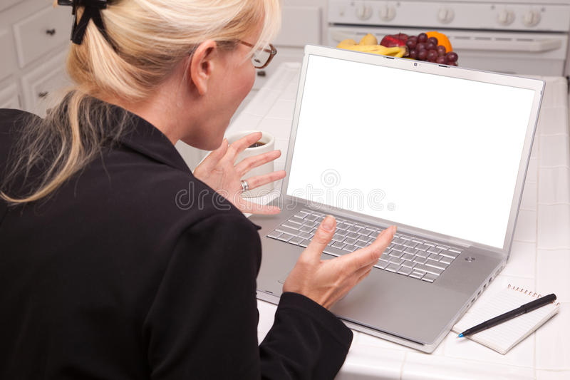 Woman In Kitchen Using Laptop with Blank Screen royalty free stock photo