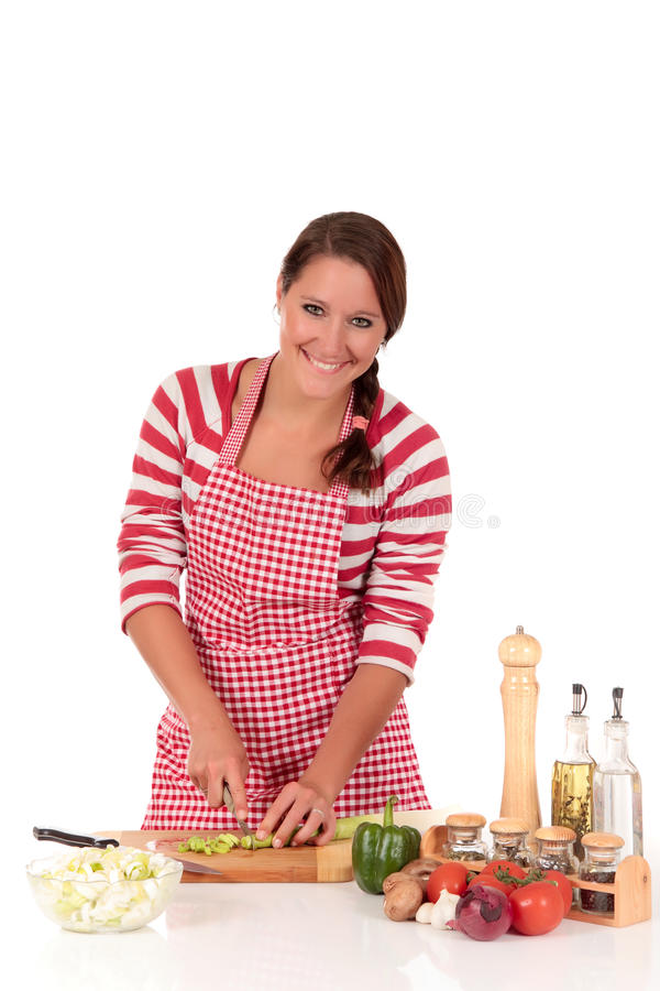 Woman kitchen vegetables. Attractive Young woman working in kitchen, cutting, cleaning vegetables, fresh leek. Studio, white background stock image