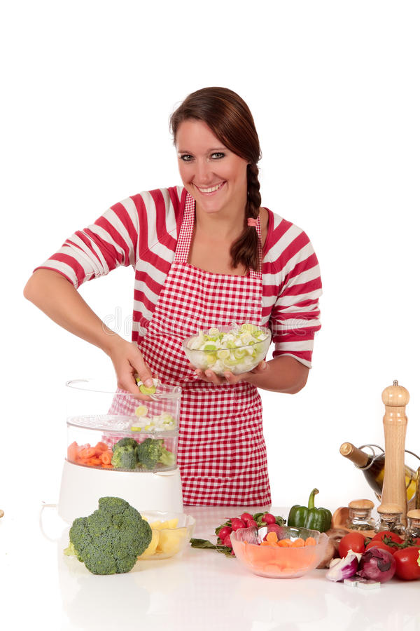 Woman kitchen vegetables. Attractive Young woman working in kitchen, preparing steamed vegetables in steam cooker. Studio, white background royalty free stock photo