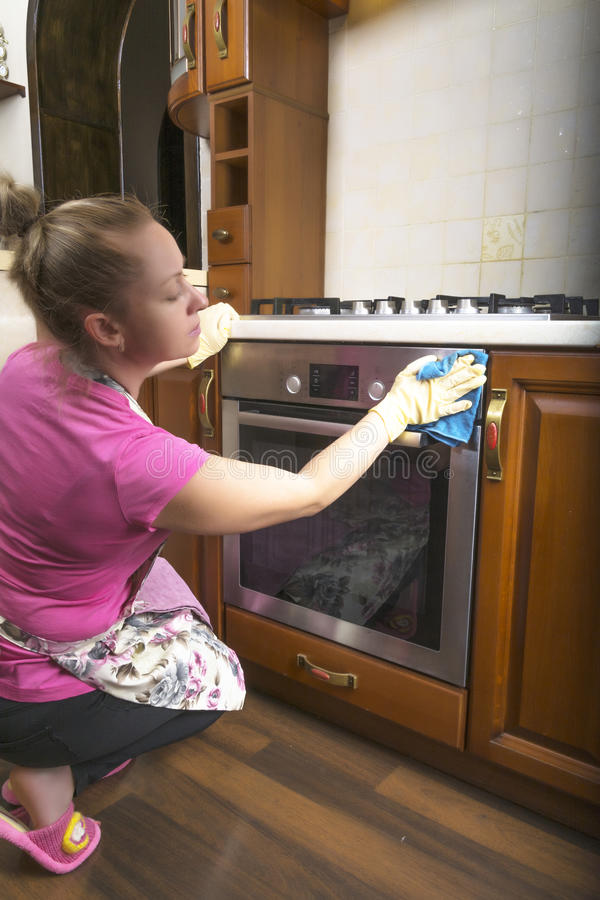 The woman in the kitchen wiping cloth on the oven. royalty free stock photo