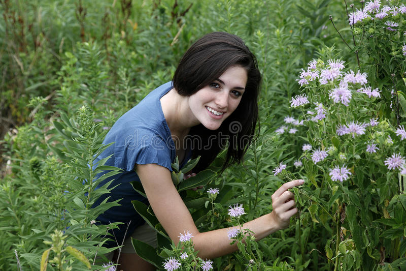 Woman kneeling in meadow royalty free stock images