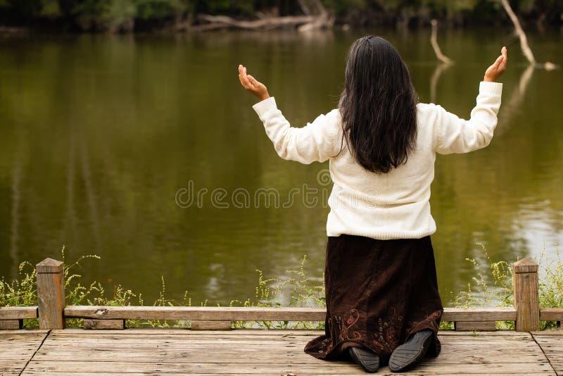 Hispanic Woman Kneeling in Prayer in Front of River in Forest Preserve. Woman Kneeling in Prayer in Front of River in Forest Preserve stock images