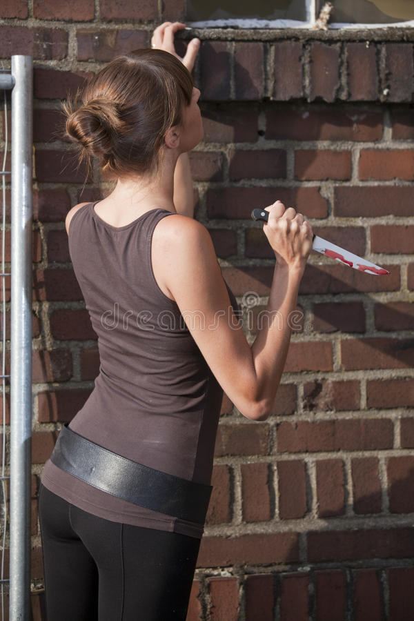 Woman with knife. Young woman with bloody knife in her hand stock images