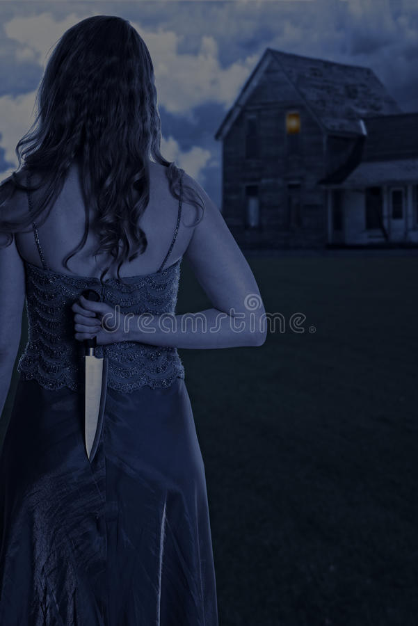 Woman with knife outside house at night. Scary woman with knife outside house at night royalty free stock photos